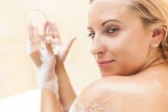 Νέο καυκάσιο ξανθό θηλυκό να κάνει Makeup κατά τη διάρκεια της διαδικασίας λουσίματος Στοκ Εικόνα