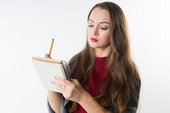 Νέο καυκάσιο όμορφο κορίτσι με το sketchbook και μολύβι στο άσπρο υπόβαθρο Στοκ Φωτογραφία