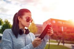 Νέο καυκάσιο playlist φόρτωσης γυναικών στην ταμπλέτα στο πάρκο Στοκ φωτογραφίες με δικαίωμα ελεύθερης χρήσης