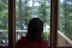 Νέο καφετί μαλλιαρό θηλυκό που εξετάζει έξω παράθυρο σπιτιών το δάσος μια βροχερή ημέρα Στοκ Φωτογραφίες