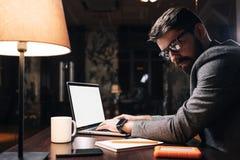 Νέο κείμενο δακτυλογράφησης διευθυντών προγράμματος στο γραφείο lap-top τη νύχτα Γενειοφόρο επιχειρησιακό άτομο που εργάζεται στο Στοκ εικόνα με δικαίωμα ελεύθερης χρήσης