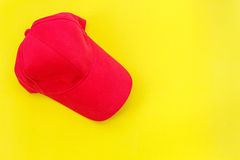 Νέο κενό κόκκινο καπέλο μπέιζ-μπώλ στο κίτρινο υπόβαθρο με ελεύθερου χώρου Στοκ εικόνες με δικαίωμα ελεύθερης χρήσης