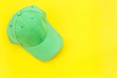 Νέο κενό πράσινο καπέλο μπέιζ-μπώλ στο κίτρινο υπόβαθρο με το ελεύθερο spac Στοκ Εικόνες