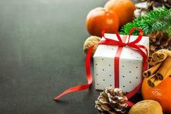 Νέο κιβώτιο δώρων ετών Χριστουγέννων με το κόκκινο τόξο κορδελλών Tangerines κλάδοι δέντρων έλατου ξύλων καρυδιάς κώνων πεύκων ep Στοκ Εικόνα