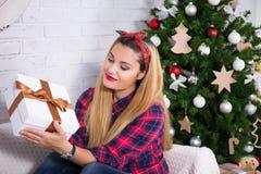 Νέο κιβώτιο δώρων Χριστουγέννων ανοίγματος γυναικών στο διακοσμημένο καθιστικό Στοκ εικόνες με δικαίωμα ελεύθερης χρήσης