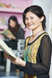 Νέο κινεζικό κορίτσι σπουδαστών με το βιβλίο στη βιβλιοθήκη Στοκ Φωτογραφία