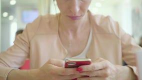 Νέο κινητό τηλέφωνο χρήσης γυναικών καθμένος στην άνετη καφετερία κατά τη διάρκεια του σπασίματος εργασίας, γοητευτική ευτυχής θη απόθεμα βίντεο