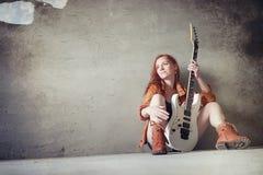 Νέο κοκκινομάλλες κορίτσι με μια ηλεκτρική κιθάρα Μουσικός βράχου gir στοκ εικόνες