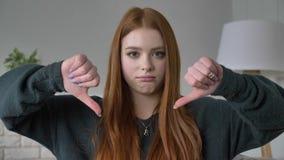Νέο κοκκινομάλλες κορίτσι blogger, πορτρέτο, που εξετάζει τη κάμερα, λυπημένος, που παρουσιάζει σημάδι απέχθειας, εγχώρια άνεση σ απόθεμα βίντεο