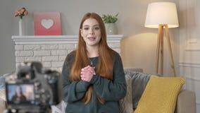 Νέο κοκκινομάλλες κορίτσι blogger που κυματίζει το χέρι της στη κάμερα, χαμόγελο, χειρονομία γειά σου, εγχώρια άνεση στο υπόβαθρο απόθεμα βίντεο