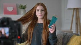Νέο κοκκινομάλλες κορίτσι blogger, χαμογελώντας, μιλώντας στη κάμερα, που παρουσιάζει νέα αγορά, σαμπουάν, εγχώρια άνεση απόθεμα βίντεο