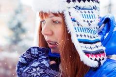 Νέο κοκκινομάλλες κορίτσι στο χιόνι Το κορίτσι θερμαίνει τα χέρια της αναπνοής Στοκ Φωτογραφία