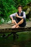 Νέο κομψό άτομο που χρησιμοποιεί το τηλέφωνο κυττάρων στο δάσος λιμνών Στοκ φωτογραφία με δικαίωμα ελεύθερης χρήσης