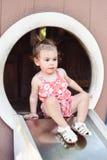 Νέο κορίτσι έξω από το παιχνίδι σε μια φωτογραφική διαφάνεια παιδικών χαρών Στοκ Φωτογραφίες