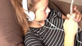 Νέο κορίτσι απορροφημένο στο άκουσμα στη μουσική φιλμ μικρού μήκους
