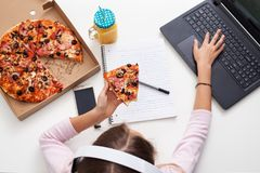 Νέο κορίτσι εφήβων που εργάζεται σε ένα πρόγραμμα τρώγοντας την πίτσα - Στοκ Φωτογραφία