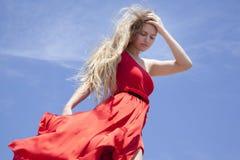Νέο κορίτσι εφήβων στο κόκκινο φόρεμα στο υπόβαθρο μπλε ουρανού στοκ φωτογραφίες