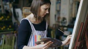 Νέο κορίτσι ζωγράφων στην ποδιά που χρωματίζει ακόμα την εικόνα ζωής στον καμβά στην τέχνη-κατηγορία απόθεμα βίντεο