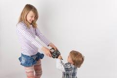 Νέο κορίτσι και ο μικρός αδελφός της που παλεύουν για τον κηφήνα μακρινό γ Στοκ φωτογραφία με δικαίωμα ελεύθερης χρήσης
