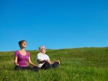 Νέο κορίτσι και παλαιά meditating συνεδρίαση ατόμων στον τομέα στοκ εικόνες με δικαίωμα ελεύθερης χρήσης