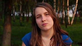 Νέο κορίτσι και συναισθήματα, πορτρέτο του σοβαρού νέου καυκάσιου κοριτσιού στο πάρκο φιλμ μικρού μήκους