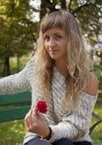 Νέο κορίτσι με έναν ροδαλό υπό εξέταση στο υπόβαθρο φύσης Στοκ Εικόνα