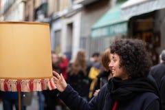 Νέο κορίτσι με ένα παλτό που παρατηρεί έναν αναδρομικό λαμπτήρα σε μια παλαιά αγορά οδών στοκ φωτογραφία