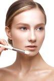 Νέο κορίτσι με ένα υγιές δέρμα και ένα Nude makeup Όμορφο πρότυπο στις καλλυντικές διαδικασίες με μια βούρτσα για την εφαρμογή το Στοκ φωτογραφίες με δικαίωμα ελεύθερης χρήσης