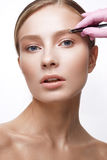 Νέο κορίτσι με ένα υγιές δέρμα και ένα Nude makeup Όμορφο πρότυπο στις καλλυντικές διαδικασίες Μαδώντας φρύδια και διαμόρφωση Στοκ Φωτογραφία