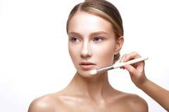 Νέο κορίτσι με ένα υγιές δέρμα και ένα Nude makeup Όμορφο πρότυπο στις καλλυντικές διαδικασίες με μια βούρτσα για την εφαρμογή το Στοκ εικόνες με δικαίωμα ελεύθερης χρήσης