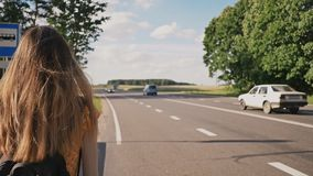 Νέο κορίτσι με μακρυμάλλες έναν ταξιδιώτη με ένα σακίδιο πλάτης που πηγαίνει κατά μήκος του αυτοκινητόδρομου Καλοκαίρι νεολαία απόθεμα βίντεο
