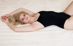 Νέο κορίτσι με με το μαύρο φίλαθλο φόρεμα που βρίσκεται στο κρεβάτι στοκ εικόνα