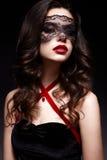 Νέο κορίτσι με μια μαύρη μάσκα δαντελλών στο πρόσωπό της και ένα κρεμαστό κόσμημα υπό μορφή καρδιάς στο λαιμό Όμορφο πρότυπο με τ στοκ φωτογραφίες