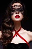 Νέο κορίτσι με μια μαύρη μάσκα δαντελλών στο πρόσωπό της και ένα κρεμαστό κόσμημα υπό μορφή καρδιάς στο λαιμό Όμορφο πρότυπο με τ Στοκ Εικόνα