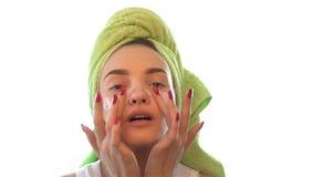 Νέο κορίτσι με μια πετσέτα στο κεφάλι που προκαλεί την κρέμα ματιών απόθεμα βίντεο