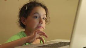 Νέο κορίτσι με τα ακουστικά που χρησιμοποιούν τον υπολογιστή για την εργασία απόθεμα βίντεο