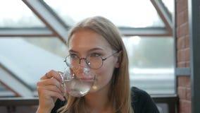 Νέο κορίτσι με τα γυαλιά που κάθεται σε μια συνεδρίαση τσαγιού και χορού κατανάλωσης καφέδων σε μια καρέκλα απόθεμα βίντεο