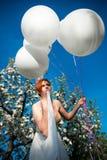 Νέο κορίτσι με τα μπαλόνια προσφοράς στοκ φωτογραφίες