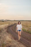 Νέο κορίτσι με τη μακριά καφετιά τρίχα που περπατά κατά μήκος του δρόμου στον τομέα Στοκ εικόνες με δικαίωμα ελεύθερης χρήσης