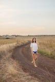 Νέο κορίτσι με τη μακριά καφετιά τρίχα που περπατά κατά μήκος του δρόμου στον τομέα Στοκ Εικόνα