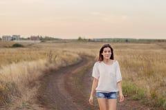 Νέο κορίτσι με τη μακριά καφετιά τρίχα που περπατά κατά μήκος του δρόμου στον τομέα Στοκ Φωτογραφίες