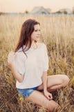 Νέο κορίτσι με τη μακροχρόνια καφετιά συνεδρίαση τρίχας στον τομέα φθινοπώρου, χαμόγελο Στοκ Εικόνες