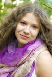 Νέο κορίτσι με τη σγουρή τρίχα στο πορφυρό μαντίλι Στοκ Εικόνα