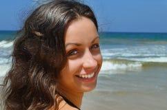 Νέο κορίτσι με τη σκοτεινή τρίχα στη θάλασσα παραλιών Στοκ Φωτογραφίες