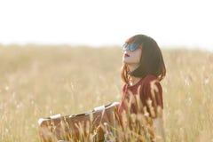 Νέο κορίτσι με τη συνεδρίαση βαλιτσών στην ξηρά χλόη Στοκ φωτογραφία με δικαίωμα ελεύθερης χρήσης