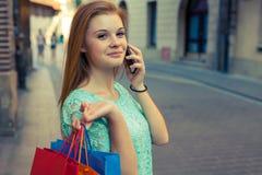 Νέο κορίτσι με τις ζωηρόχρωμες τσάντες αγορών που καλούν το φίλο της Στοκ Φωτογραφίες