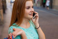 Νέο κορίτσι με τις ζωηρόχρωμες τσάντες αγορών που καλούν το φίλο της Στοκ εικόνες με δικαίωμα ελεύθερης χρήσης