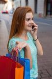 Νέο κορίτσι με τις ζωηρόχρωμες τσάντες αγορών που καλούν το φίλο της Στοκ φωτογραφία με δικαίωμα ελεύθερης χρήσης