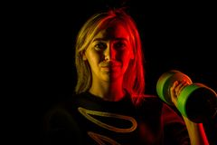 Νέο κορίτσι με τους πράσινους αλτήρες στα χέρια της εγκαίρως για τον αθλητισμό και workouts με το δευτερεύοντα φωτισμό κίτρινος κ στοκ εικόνα