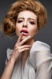 Νέο κορίτσι με το μεθύστακα hairstyle και σύνθεση Nude Όμορφο πρότυπο με τα τσέκια στα φρύδια και το ευγενές ρόδινο μανικιούρ στοκ εικόνες